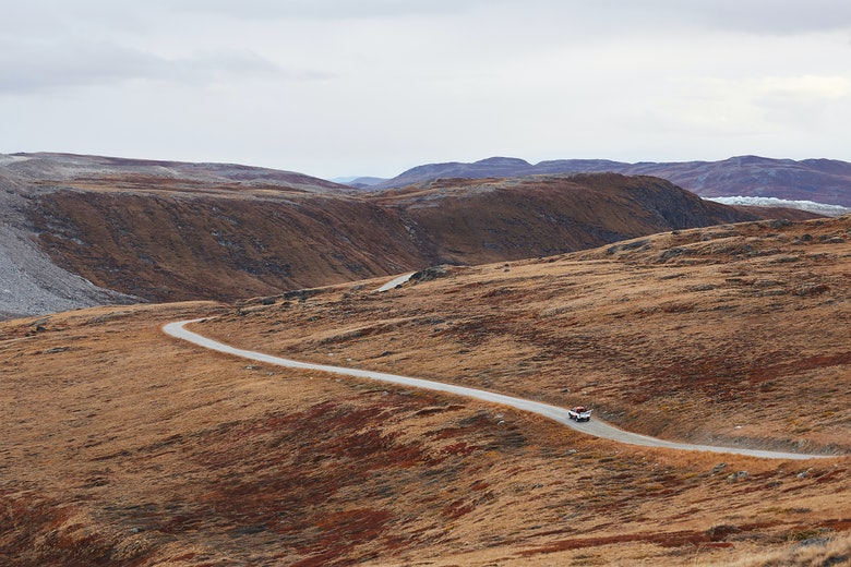 Photo from above of a car driving on a road through the nature near Kangerlussuaq